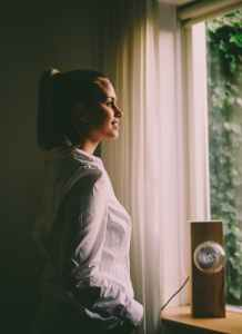 woman wearing white long sleeved shirt standing in front of the window with white curtain